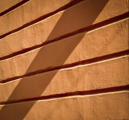 old orange wall with relief in the shade