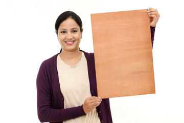 Smiling young Woman holding blank wood sheet