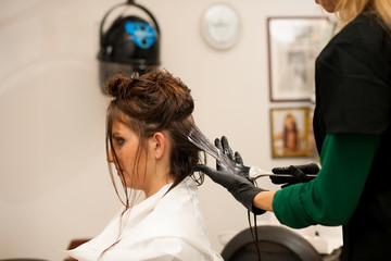 Hairdresser making hair treatment to a customer in salon