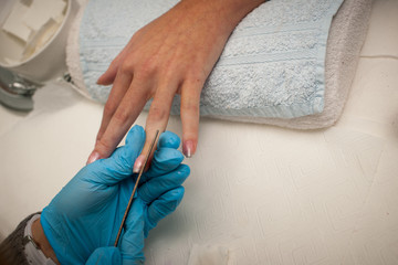 Making hand nails in a professional hand care salon - manicure