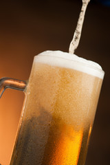 Big glass with handle filled with fresh beer with a lot of foam