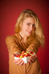 Beautiful young caucasian blonde woman holds a delicious fruit s