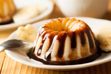 Vanilla pudding with dessert with chocolate syrup and banana sli