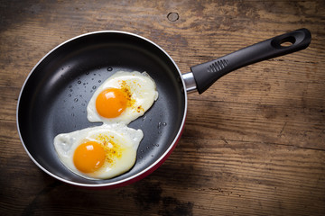frying eggs in pan on table