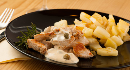 Grilled turkey meat with cheese sauce and capers on black plate
