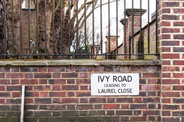 Ivy Road Leading to Laurel Close Street Sign against Brick Wall