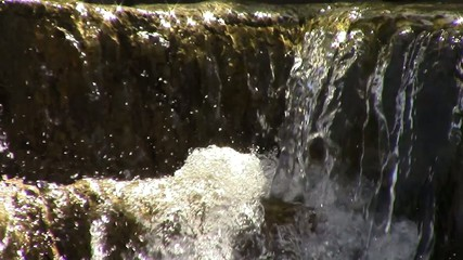 Motion background with water splashing on the rocks.