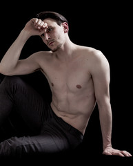 Bare-chested man portrait sitting and thinking