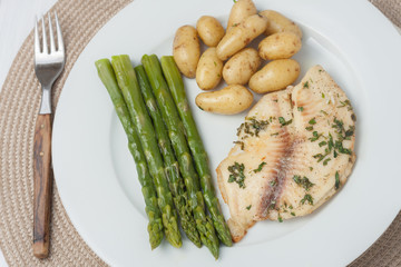 cooked fish with parsley servied with asparagus and baby