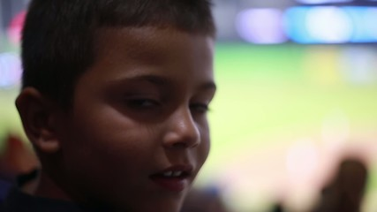 Cute kid at baseball stadium looking to camera and then to game