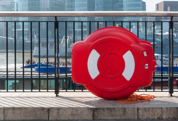 Lifebuoy attached to metal railing on river Thames, London, UK