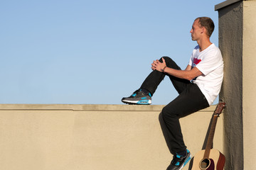 Man seated on ledge looking into distance with guitar