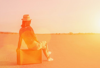 Traveler woman sitting on suitcase on road at sunny day