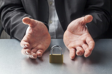 businessman hands displaying padlock at work