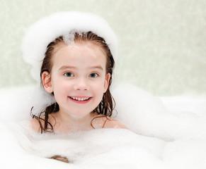 Smiling little girl washing in bath