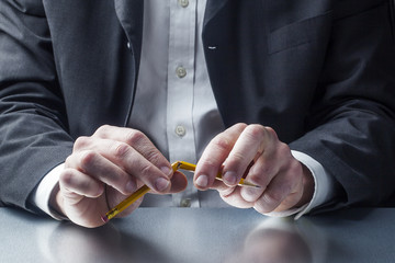 male manager with pencil broken in his hands on the workplace