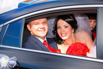 The bride and groom have fun behind the wheel of retro car. Wedd