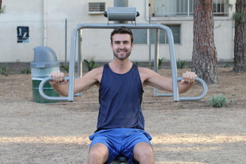 Athletic lean man executes exercise in outside sport gym