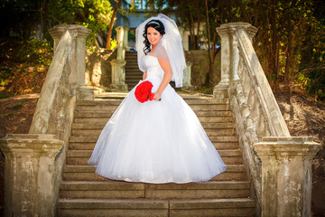 Beautiful bride sits on the stairs of the old church