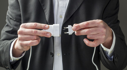 male businessman hands plugging electrical cord together
