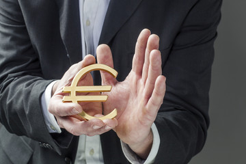 businessman caring for Euro symbol in his hands