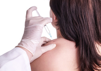 Young woman gets injection in the upper shoulder - neck