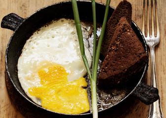 fried eggs in a frying pan with rye bread