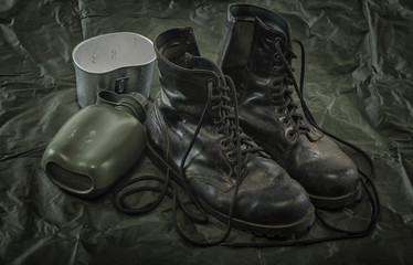 old combat boots and military canteen