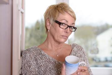 Ernste blonde Frau mit einem Becher