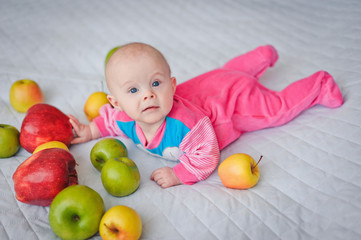 Cute baby surrounded by bright beautiful large fresh apples