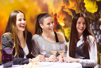 Three beautiful women having fun in a wine bar