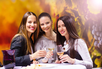 Three beautiful women having fun in a wine bar