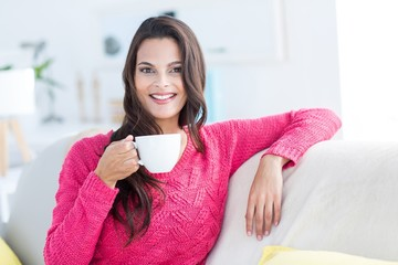 Smiling beautiful brunette relaxing on the couch and holding mug