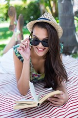 Smiling beautiful brunette lying and reading a book