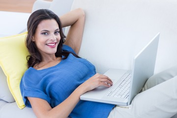 brunette relaxing on the couch and using her laptop