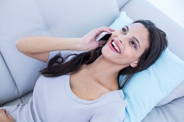 brunette relaxing on the couch and speaking on the phone