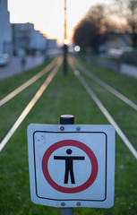 sign for pedestrians in front of tram rails