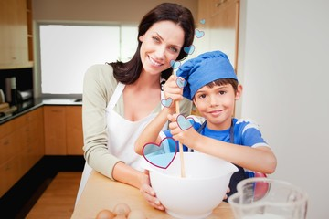 Composite image of mother and son having fun preparing dough