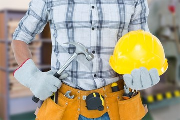 Composite image of handyman holding hammer and hard hat