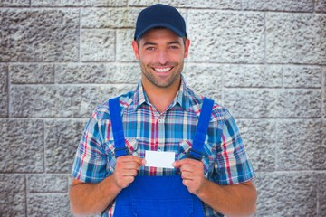 portrait of happy handyman holding visiting card