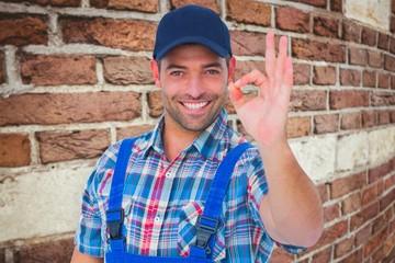 Composite image of portrait of smiling repairman gesturing okay