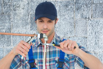 Composite image of plumber fixing pipe over white background