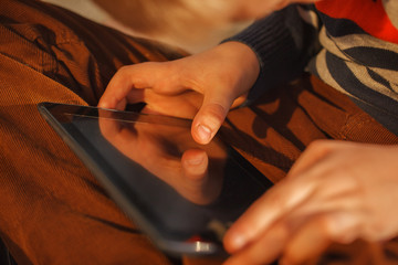 Close-up of kid's hands close up holding  digital tablet