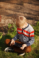 cute boy sitting on grass in park and playing with tablet