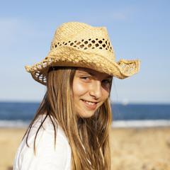 Niña con sombrero de paja en la playa