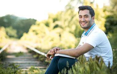Smile student or man sitting in nature with book