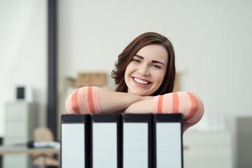 lächelnde junge frau stützt sich auf aktenordner