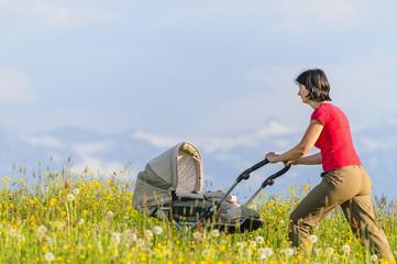 Mutter schiebt Kinderwagen im Frühling