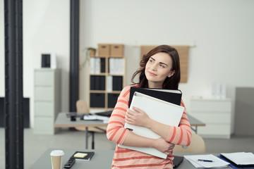 lächelnde frau im büro hält aktenorder in den händen