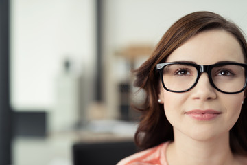 junge frau mit brille schaut in gedanken nach oben